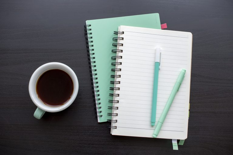 Mint green open notebook and a cup of coffee